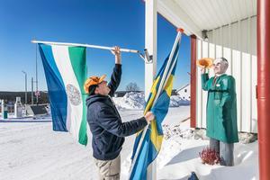 Edward van Munster sätter upp flaggorna på fasade och gör sig redo för en arbetsdag i affären.