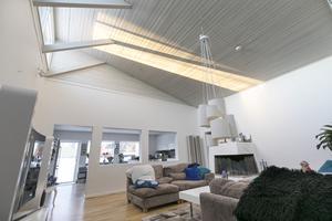 Närmare fem meter i takhöjd och stora fönster ger ett påtagligt ljusinsläpp i vardagsrummet.