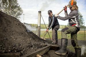 Thomas, 40, och David, 15. Båda stortrivs med det gamla hantverket. I början har milan brantare ytterväggar, men allteftersom veden blir till kol sjunker den ihop. Då får man vara med och banka så att väggarna förblir täta.