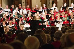 Världens Jul 2013 med sångare och orkester. I år samarbetar Samklang med andra körer men åter med Sundsvalls Blåsorkester.