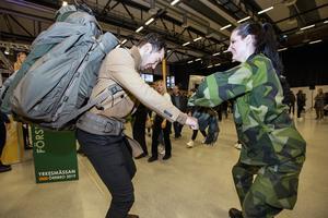 Javad Afari fick hjälp av försvarsmaktens Emma Nord att pröva en jägarsoldats ryggsäck.