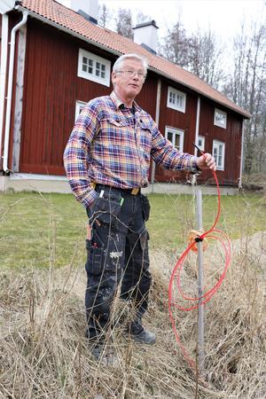 Olli håller upp fiberslangen som legat och skräpat vid tomtgränsen i Ormesta sedan förra året.