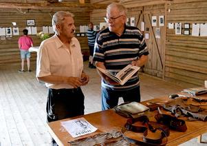 Tommy Syvertsen och Gossas Sven-Olle Axelsson vid ett bord med en del föremål med anknytning till verksamheten i Älgbergslägret.
