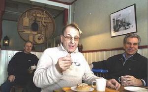 Åke Kock njuter av en semla på Fricks konditori på Fettisdagen i går. Bredvid honom sitter Kent Andersson och han som täcker upp där bak är Stig Mases.FOTO: MATS LINDSTRÖM