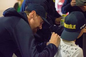 SSK:s Alexander Sahlin signerar en ung supporters tröja.