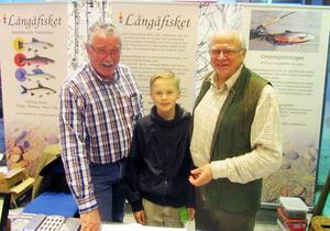 Börje Björk, Viktor Settling och Helge Jonsson i Långåfiskets monter. Viktor, nybliven tioåring, tog i somras sin första flugfångade öring i Djuptjärn.