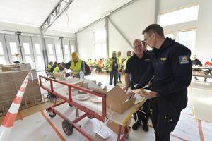 Per-Erik Jansson och Mattias Jensen hugger i på smörgåstårta men snart flyttar brandbilarna in i nya brandstationen.