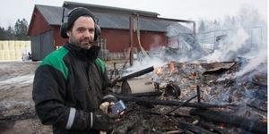 Fredrik Rosenblom framför resterna av ladugården, dagen efter branden.  I bakgrunden syns gårdens djurstall.