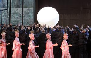 Barnen i sina rosa kostymer bär in månen, medan kören bildar en svart bakgrund med sina bylsiga svarta dunjackor.