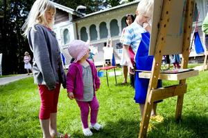 """KALLT MEN ROLIGT. För de barn som ville erbjöds målning vid staffli. Gusten Holmgren, snart sju år, från Strömsbo, målade en bil. Syster Lydia och kusinen Svea-Maria tittade på. """"Vi har åkt Snoddaståget, det var roligast i dag, men väldigt kallt"""", berättar Lydia."""
