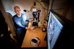 Markus undersöker två hylsor i mikroskop för att se om de skjutits från samma vapen.