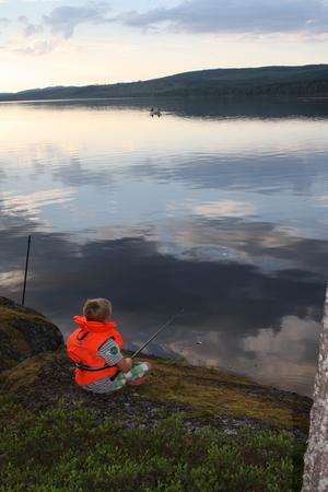 Elias fiskar vid kanten av Betasjön i Junsele. Tittar man ut över sjön så ser man hans mamma och pappa ute i båten.