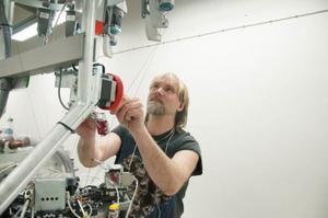 Håkan Eriksson vid sin stickmaskin med 170 nålar som ska producera långkalsonger. Plaggen rundstickas eftersom det är viktigt att ha så lite sömmar som möjligt.