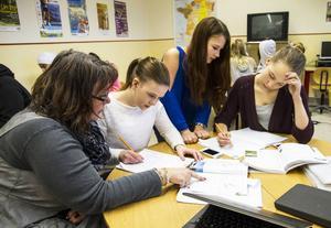 Elevassistenten Anna-Karin Mohlin hjälper sjundeklassarna Miranda Wikström, Anna Krantz och Anna Wikberg med matten.