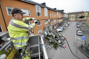 Med van hand hänger Göran Bengtsson från One Nordic hänger upp årets julgirlander på Trädgårdsgatan i Kumla. Sin första girland satte han upp i Nora för 32 år sedan.