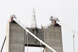 Två av Trafikverkets anställda plockar ner Nordfronts flagga som placerats på toppen av pylonen vid Hornöberget.