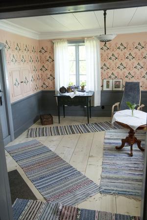 Väggarna i salen är lerklinade och målade. Grundfärgen är rosa och sedan schablonmålad med ett mönster som familjen hittade på nocken i övervåningen som troligen varit i salen, parstugan hade ju inte någon övervåning.
