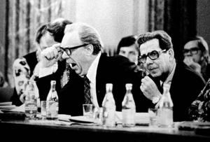 """Gösta Sandin, tung S-politiker i Sandviken. Det blev en utdragen landstingsdebatt i Gävle stadshus 1975. Jag kom i slutet av mötet. Alla var slitna, trötta och ville gå hem. Det var det jag skulle illustrera. Gösta gäspade. Tack, tänkte jag, bilden var bärgad. Nästa dag fortsatte diskussionerna, då passade jag på att ge Gösta en kopia. Gösta talade lite grann som gamle finansministern Gunnar Sträng. Gösta sa lite barskt, """"Bilden är signifikativ för debatten men jag ska sparka dig på tasken någon gång""""."""