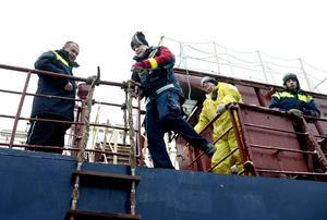 Lotsen Magnus Bergström kliver ut över kanten och till lejdaren, stegen, som hänger ner efter fartygets sida. Styrman på M/T Nordic Nora och två matroser säger hej då.