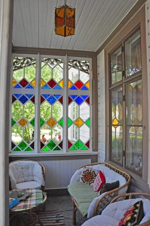 Verandan som möter besökarna i entréingången har målade fönster i blått, rött, gult och grönt.