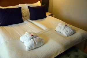 Quality Hotel. På sängen finns det badrock, tofflor och en chokladpralin.