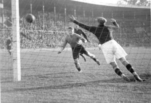 Danskdödaren slår till. Bertil Ericsson nickar in ett av sina fyra mål mot Danmark i Idrottsparken i Köpenhamn förbi den danske målvakten Svend Jensen – 30 000 ser på, och tystnar, den 17 juni 1934.