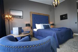 Marinblått är ett genomgående tema i rummen. Lite galna och udda detaljer som en golvlampa i en burliknande ställning, ger en personlig charm.