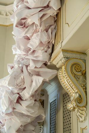 En maffig utsmyckning av papper sträcker sig från golvet upp på läktaren.