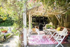 Under pergolan har Sara möblerat med äldre trädgårdsmöbler som hon fyndat.
