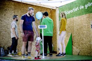 Miljöpartisten Niclas Persson och sonen Joar Nilsson inspekterar partiets scen på Demokratins torg.