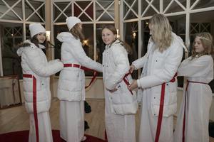 Tärnorna Thea, Jenna, Mathilda,  Amanda och Emma gjorde sig redo för luciakortegen. Det tog på sig varma kläder. Här hjälper de varandra med att få ordning på de röda sidenbanden.