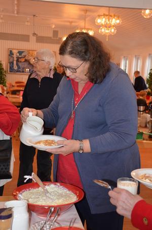 Det fanns gott om hjälpande händer ifall man hade svårt att hämta gröttallriken själv. Här är det diakon Ellen Sjölander som hjälper till att fylla på mjölk.