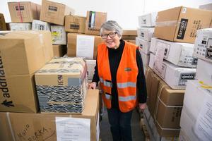 Kersti Jobs Björklöf bland några av alla lådor som lagts på pallar.