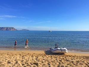 Foto: Familjen Sahlén. Båten ligger i en fin vik och familjen tar jollen in till sandstranden.