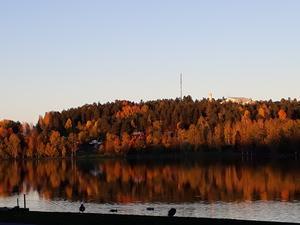 Höglidenberget i höstfärger speglar sig i Lillfjärdens vatten på eftermiddagen den 5 oktober.