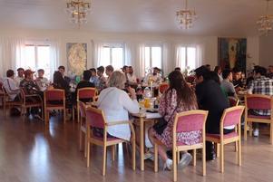 En måltid intas i Bromansalen på St Jakobsgården. Knytkalas bidrag från kontakpersoner och värdfamiljer men med afghansk lammgryta tillagad av Mozhgan som det mest uppskattade bidraget.