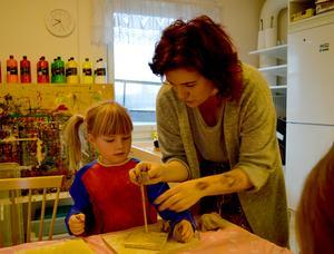 Pia visar Hedwig hur man också kan bygga med leran på höjden på en träplatta med pinne.