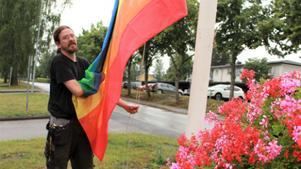 Robert Forsberg från Nybo hissar flaggan på Gammeltorpsvägen. Foto: Nykvarns kommun