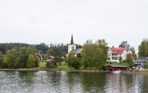 Revsunds kyrka med dess prästgård. Utanför betar några lamadjur.