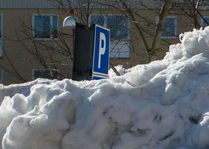 Man kan se att det finns en skylt bakom snöhögen på att det ska vara en parkering.