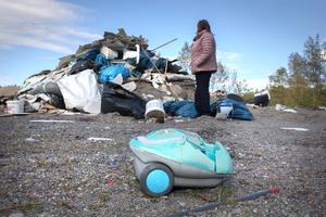 En liten leksaksdammsugare i plast ligger hjälplös framför en av de stora högarna med kläder, dvd-skivor, kläder, byggmaterial, bildelar och trasigt porslin.