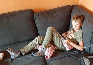 Barnbarnet Charlie spelar TV-spel i soffan.