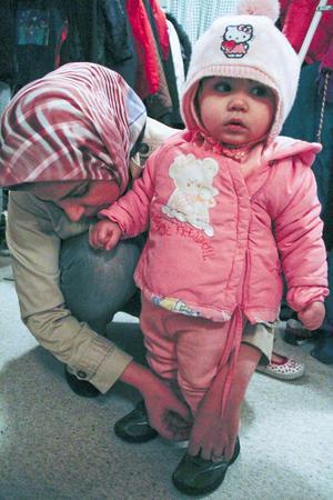 Lilla Nazani, 1 år, får hjälp av mamma Leyla Husseiny att prova nya skor.