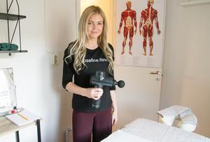 Josefin Öberg med en massagepistol så kallad triggerpunktsmassage som behandlar knutar.