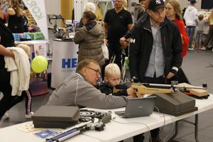 Tommy Hofberg visar Måns Wikehult vad man ska tänka på vid luftgevärsskytte. Vid sidan om står Henrik Wikehult.
