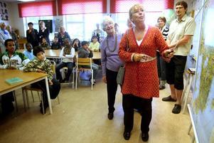 Chris Heister visar Västerbotten på kartan för skolbarnen. Där är hon landshövding. I bakgrunden Lilly Hansson och lärarna Margaretha Andersson och Jonas Larsson.