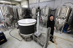 Erik Sahlin framför anläggningarna där ölet tillverkas. Sex tankar med en kapacitet i varje  på 1 000 liter.