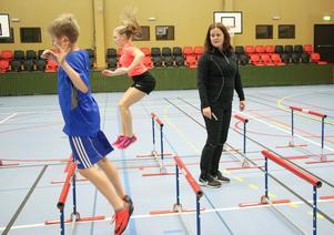 Monika håller ett öga på när Gunnar och Nanna tränar häcklöpning i Närlundahallen.