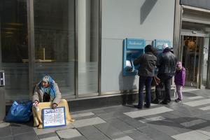 En kvinna tigger utanför en bank i Stockholm. Foto: JANERIK HENRIKSSON / TT