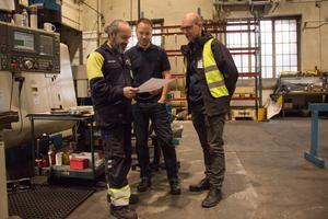 Basem Habib visar ritningen för verksamhetschefen Johan Wihrén och yrkesläraren Morgan Åkesson.